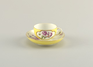 Cup with simple loop handle; saucer deep, with curved sides.  Inside of cup and saucer white, with scattered flowers; outside of cup and underside of rim of saucer yellw, with white reserve panels, on cup, in which are flowers.  Edges of cup and saucer brown.