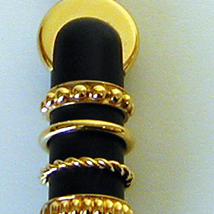 Gilt bronze knife with black handle decorated with four gilt rings, terminating at flat gilt disc.