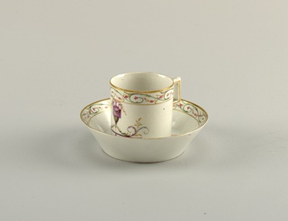 Cylindrical cup, rectangular strap handle. Flat saucer with flaring sides. Decoration in pale colors, of an urn with foliate rinceaux, and bands of foliage in colors and gilding.