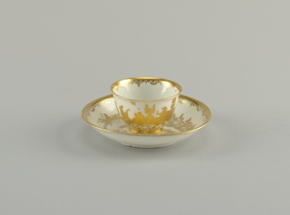 Round, tapering form cup with circular ring foot that has gold chinoiserie decoration on the surface.  Images of figures engaged in various activities such as eating, drinking, and playing instruments are in the center and birds, monkeys, and a rat are included in the scene.  Interior rim of the cup is decorated in a gold scalloped border with lines and scrolls.  The saucer is a basic round form with faded gold chinoiserie decoration in the center and a gold scalloped bordered with lines and scrolls around the edge. In the center of the saucer, there are two figures, a palm tree, scroll decoration and other forms of foliage.