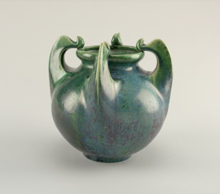 Bulbous form, with four regularly spaced, curved, handle-like protrusions that rise from vase shoulder, terminating on wide lip at top where they fold back on themselves at tips, assuming stylized whiplash forms; mottled blue-green and red flambé glaze applied to surface.