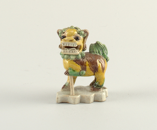a) On grey-white cloud-shaped base, the animal stands with mouth open, one foreleg raised with lion cub as support. A small vertical tube at rear of animal for joss stick. Predominantly yellow glaze, with brown, green and black details.  b) Almost identical; raised foreleg is supported by a rod from which ball is missing. Read vertical tube missing.
