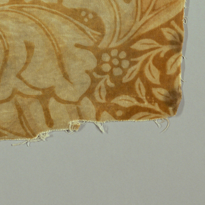 Symmetrical pattern of large curving leaves with small leaves and flowers between, in tan on an ochre ground.