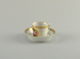 Cylindrical; saucer flat with flaring sides. Strap handle of rectangular form. Floral medallion.