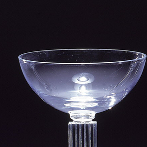 Narrow glass with stem resembling fluted column with wide foot.