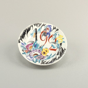 """Circular, slightly shaped edge; the inscription """"1921"""" intersperced among stylized floral motifs"""
