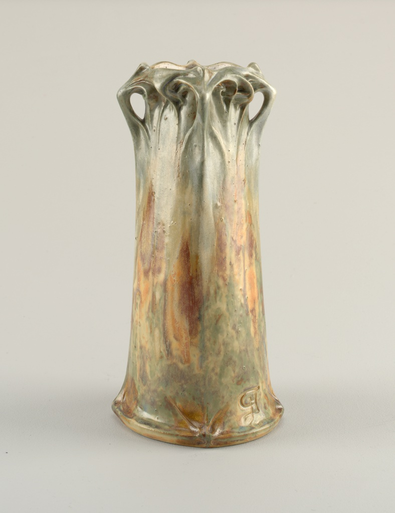 Tall cylindrical body, slightly flared and squared at base, rising to a system of abstract scrolls and free form projections at the slightly squared mouth. Glazed in mottled brown, rust, and grey-green.