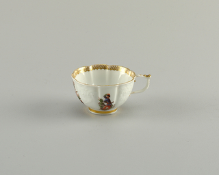 Lobed cup with round foot and slim handle. Indistinct molded floral decorations. Diaper pattern gilding interior rim and solid gold band at foot. Unmolded panels painted with figures including the Commedia dell'arte zannie Harlequin, who has a slapstick in his belt.