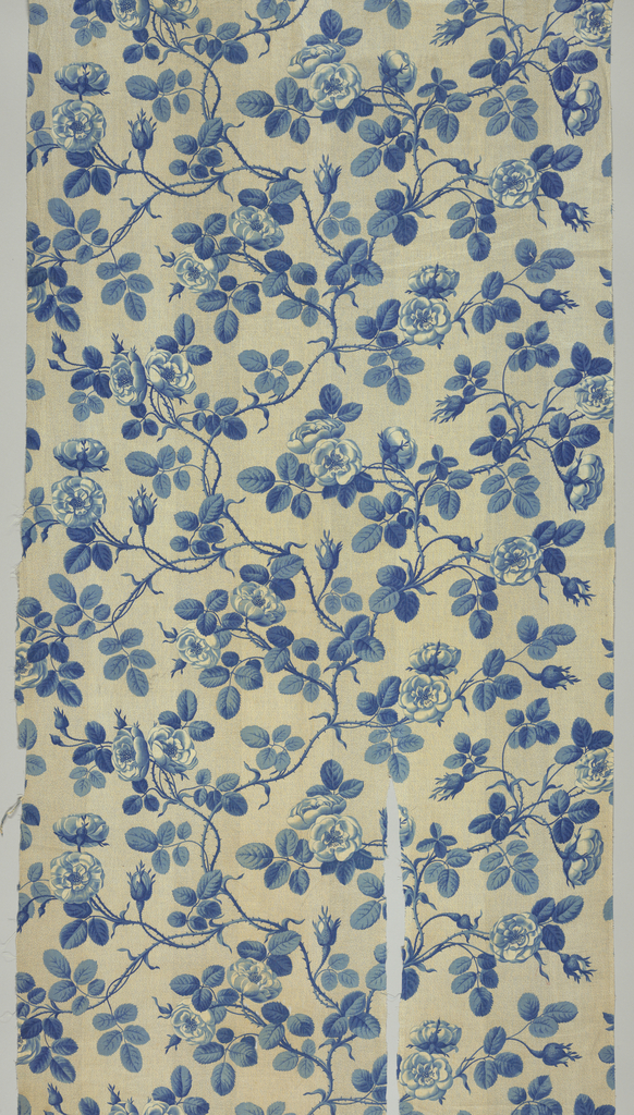 Continuous meandering rose vine in blue on a speckled gray background. The repeat unit fills the full width of the fabric. Straight repeat.