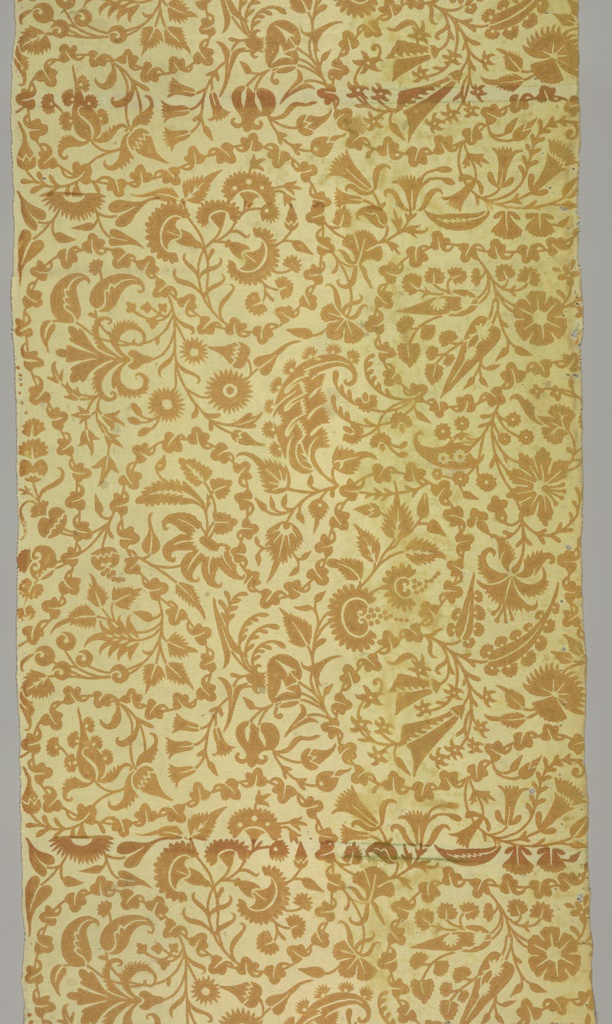 Densely scrolling leaves and flowers in brown on a yellow/cream background.