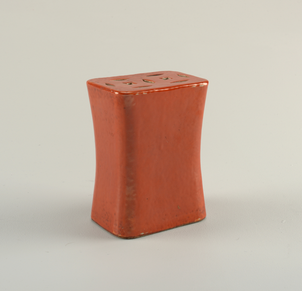 Parts a & c) Tall rectangular shapes with slightly concave sides. Oval opening in bottom, ornamental piercings on top.  Coral red glaze.  Parts b & d) Rectangular carved wooden stands.