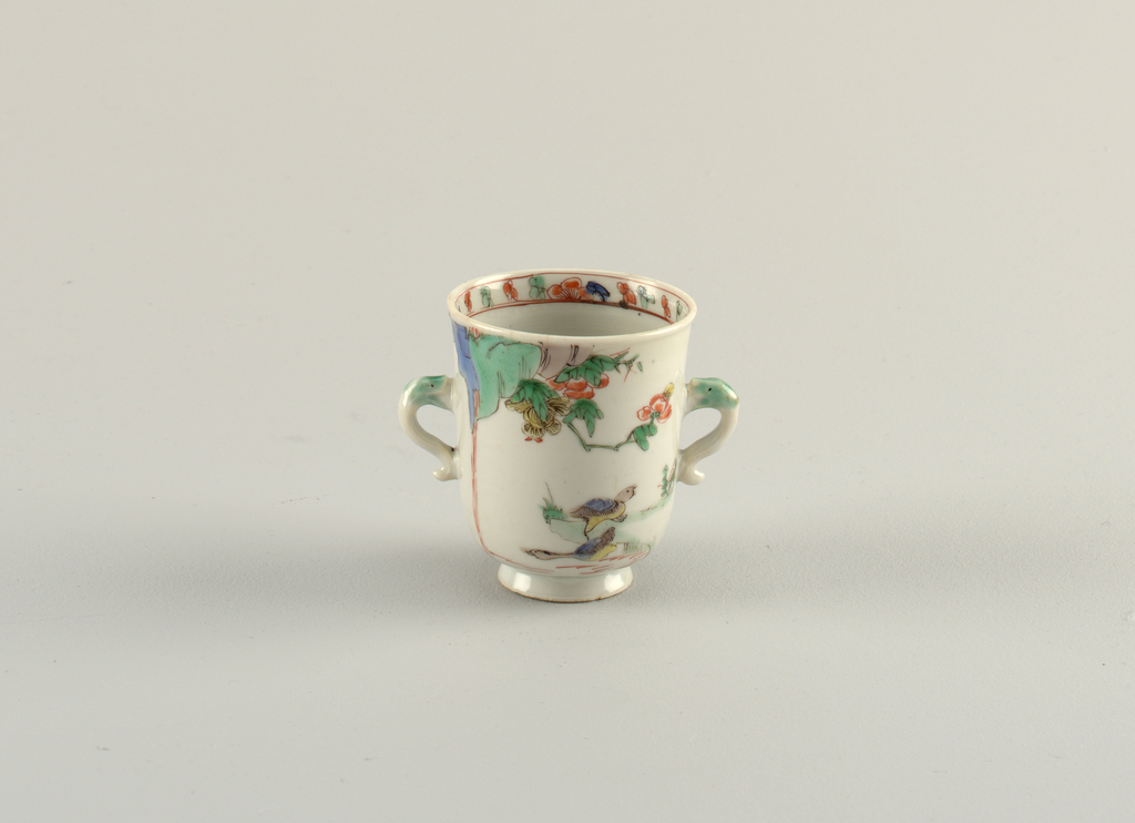 Famille verte footed beaker with two dolphin-form handles. Painted florals with birds; painted band of ornament inside the rim.