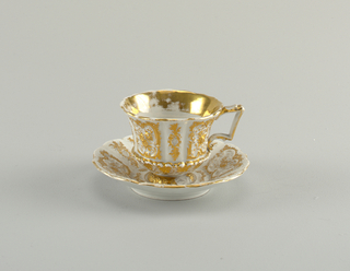 Cup with rounded foot and round bottom marked by ridge, and convex sides; flattened handle with scrolls. Saucer paneled, like upper part of cup, with eight alternately wide and narrow panels. Crisp Rococo revival relief decoration of scrollwork and flowers gilded. Gold band and inside of cup.
