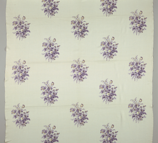 Sample has a white ground printed with a widely-spaced repeat of floral bouquets in shades of purple and yellow with minor details in black. Both selvedges present.