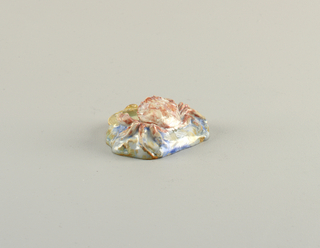 Figure of a crab on rock-like base, claws resting on shell which forms small disg. Mottled glaze, some crystalline glaze. Crab pink, shell cream-colored, base blues, greens, cream.