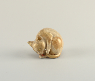 Figure of a cat, curled about himself, licking back paw.  Satsuma style, cream-colored small crackle glaze, with painted streaks of brown and gold, tongue painted red.