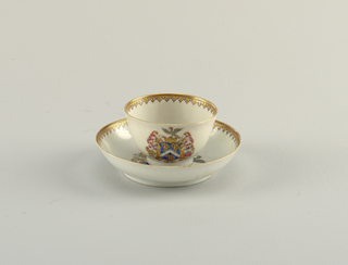 A Chinese export armorial tea bowl with matching saucer bearing crowned arms with birds, within a scrollwork cartouche. Gilding at rims.