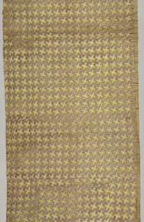 "Fragment of a quilt: top fabric a small scale all-over pattern of violet bows and ribbons forming a square diamond grid the interspaces of which are alternately tan and yellow. Stuffing is a natural cotton and the backing fabric is yellow ochre cotton 2/2 twill. Quilting pattern at one side forms a border with a slightly curving leafy vine between a group of narrow bands on each side and for the ""field"" a square diamond grid. Running stitch in quilting through three layers"