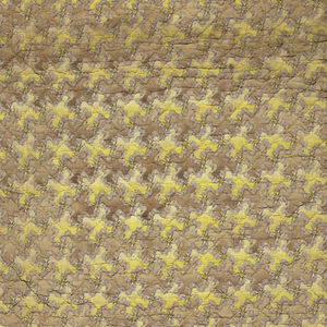 """Fragment of a quilt: top fabric a small scale all-over pattern of violet bows and ribbons forming a square diamond grid the interspaces of which are alternately tan and yellow. Stuffing is a natural cotton and the backing fabric is yellow ochre cotton 2/2 twill. Quilting pattern at one side forms a border with a slightly curving leafy vine between a group of narrow bands on each side and for the """"field"""" a square diamond grid. Running stitch in quilting through three layers"""