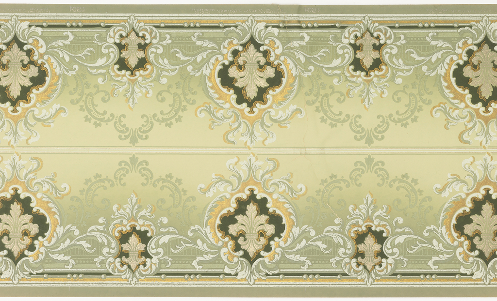 Border printed two across the width. Design contains alternating large and small foliate medallions, each containg an acanthus fleur de lys. Background sahdes from light tan at the top to darker green at the bottom. Beading along bottom edge. Printed in shades of green, white, and metallic gold.