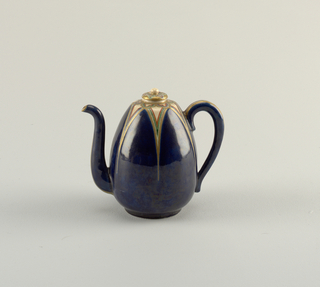 "Ovoid shape. Curved spout and loop handle. Clear crackle glaze on buff body. Deep blue enamel in form of six petal-like sections on shoulder, outlined and decorated with ""jui-i"" forms of gold, green, blue, red. Gold lines on underside of spout and handle. Underside of foot glazed. Stopperlike cover with similar ""jui-i"" design on gold reserve. Round knob."