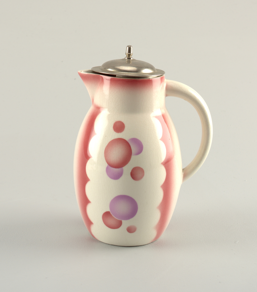 Bulbous cylindrical pitcher narrowing at the top to a flat-sided circular band with protruding spout sitting across from a c-shaped handle.  White background with airbrushed rose-color on top edge and in four vertical scalloped bands running equally spaced down the sides.  These scallops form two panels on either side of the jug containing overlapping circles of rose and lavender.  Metal domed lid with a tall finial and strained below.