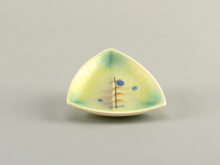 Triangular dish with curved sides and raised bottom rim.  Cream ground with green at corners and overlying speckles of yellow, bisected by faint blue line. Center airbrushed design of three wavy brown lines, five black straight crossed lines, and three blue dots.