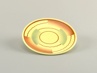Circular plate with raised bottom rim.  Yellow background with straight and wavy brown lines forming concentric circles broken up by semi-rectangular swatches of airbrushed brown and blue.