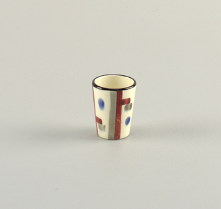 Small cylindrical cup.  Pale cream ground with black lining the lop edge and a surface patterning of burgundy and gray lines with blue dots.