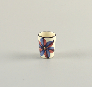 Small cylindrical cup.  Pale cream ground with mouth lined in black.  Burgundy and blue flower with off-shooting rose and black ribbon-like trails.