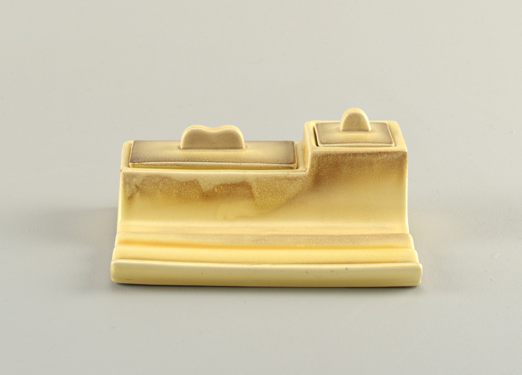 Rectangular well with raised compartments and a grooved tray in the front.  Left compartment is rectangular with two interior compartments and lid with camel hump finial.  Right compartment contains squat cylindrical glass ink cup and has a square lid with semi-circular finial.  Yellow background with airbrushed brown lining the edges of the raised compartments and the lids.  Airbrushed brown and orange decorate the tray's grooves.