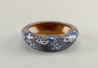 Circular form with inward curving lip.  Interior glazed brown with central circular design of stylized blue-berry vines of green and black.  Exterior glazed blue with abstract patterns consisting of circles, squiggly lines, and curling shapes all in white, green, tan, brown, black, and white.