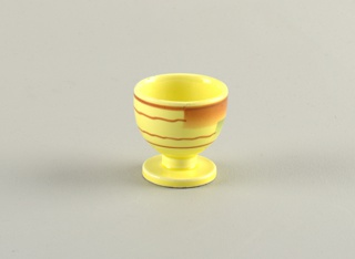 Circular cup on raised circular stand.  Yellow background with pattern on cup area of two wavy brown lines bordered by two straight brown lines all running horizontally around the cup, broken once by airbrushed rectangles of brown and blue.