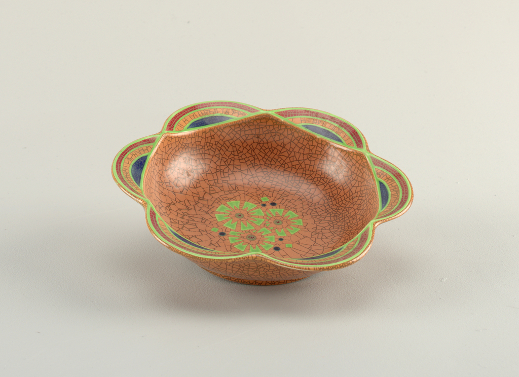 Circular form with six-sided lobed rim.  Tan to brown crackle glaze; floor of bowl decorated with three stylized flowers in shades of light and dark green; each lobe with curved bands of light green, red and blue.