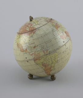 Biscuit container as globe. Globular form with circular, domed hinged lid; decorated overall with polychrome map of the world, the continents and countries picked out in shades of yellow, orange, pink; grid and names of oceans, countries, and geographical features printed in black; small brass handle on lid, three brass ball-shaped feet at base.