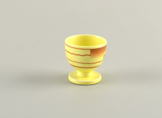 Circular cup on raised circular stand.  Yellow background with pattern on cup area of two wavy brown lines bordered by two straight brown lines all running horizontally around the cup broken once by airbrushed rectangles of brown and blue.