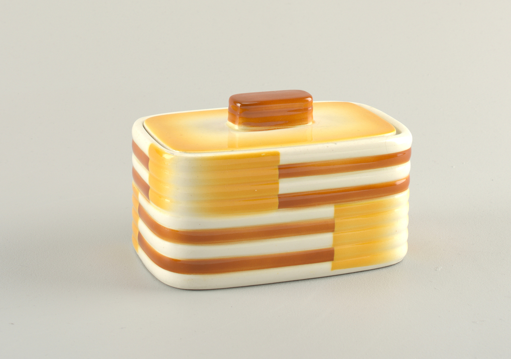 Rectangular box with streamlined corners. Flat lid with rounded rectangular handle. Orange and yellow geometric decoration.