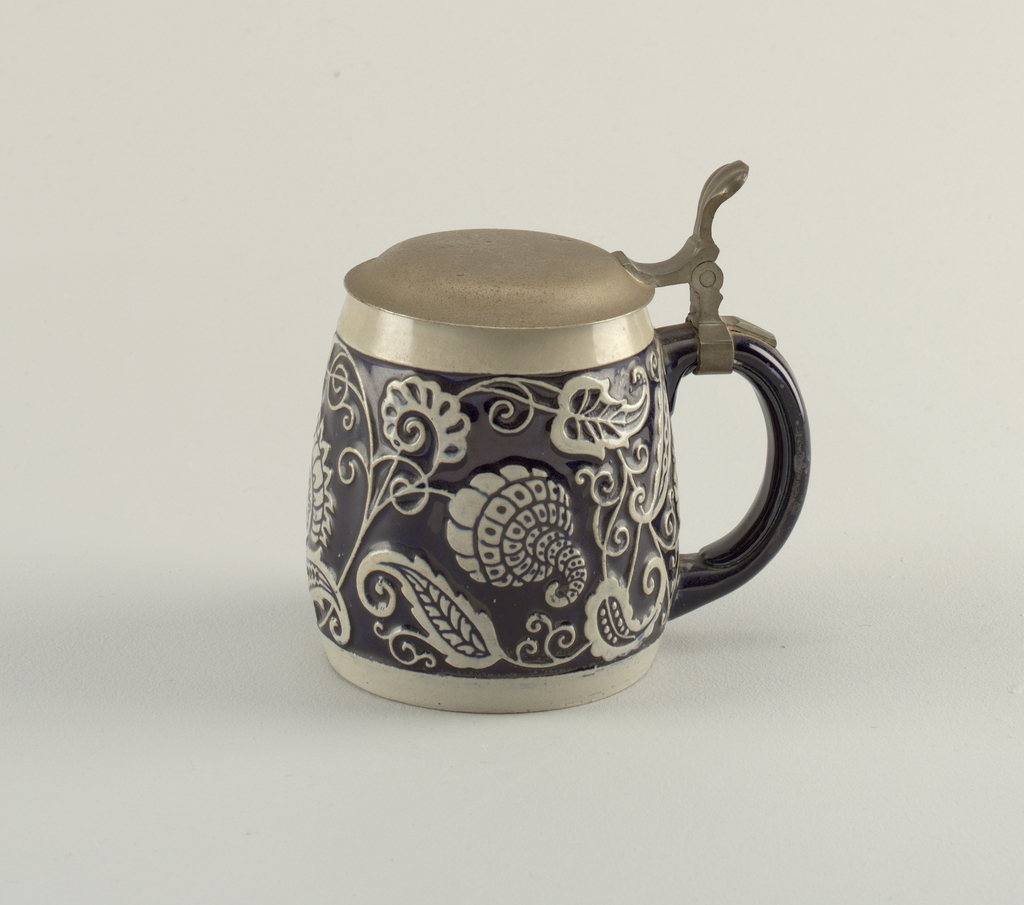 Bulbous, cylindrical form wider near the middle with a joined c-shaped handle.  Capped by a round convex pewter lid attached at the handle with an outgrowing plume.  Gray ceramic body covered in the middle and on the handle with dark blue.  Surface decoration consists of raised stylized flowers, vines, and leaves all in gray.