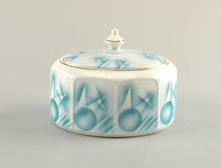 Octagonal cookie box with oval rim lined in gold.  White background with decoration of airbrushed turquoise circles, lines, and angles, on the eight relatively flat sides.  Oval lid with a pointed finial with a gold line around the top outside edge of the finial.  Also, a white ground on the lid with four airbrushed patches of turquoise-outlined angles.
