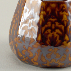 Low faceted vase with orange and brown pomegranate pattern glaze.