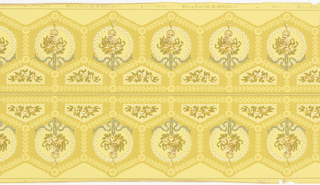 This frieze features hexagonal medallions arranged in a honeycomb pattern. The edges of the medallions are stylized laurel leaves with blossoms at the corners. Within each medallion is a round wreath of flowers and a basket of flowers hanging from a blue ribbon. The pattern mirrors itself across a central dividing line. This design is printed in shades of yellow, blue, green, white and brown on a beige ground.