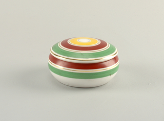 Circular bowl with inward curving lip.  White background with horizontal lines of red, green, and gold on the top half of the surface.  Dome-shaped lid with concentric circles of yellow, red, and green alternating with white circles highlighted with gold.