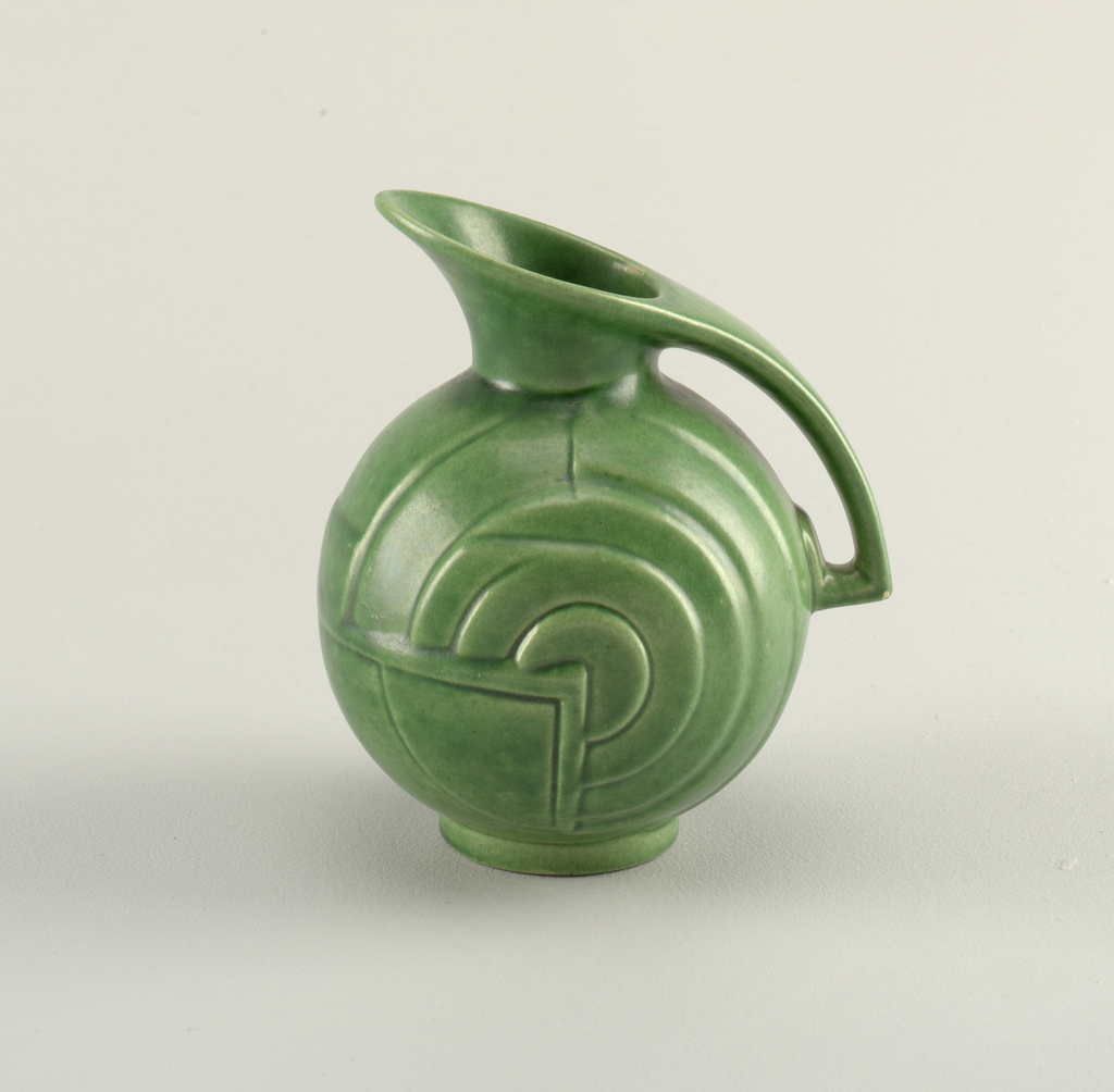 Round body on ring foot. Angles spout that extends to form the handle. Molded decoration showing concentric circles. Green glaze.