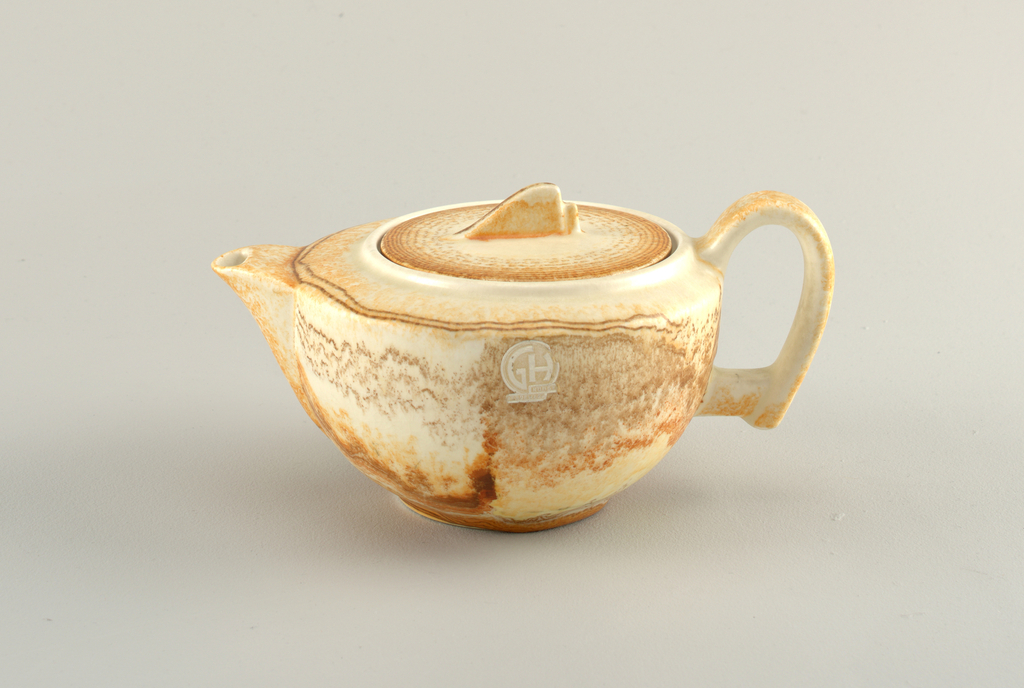 Oval shaped body with a flat lid and ear-shaped handle. It's color is a mix of browns, whites and red.