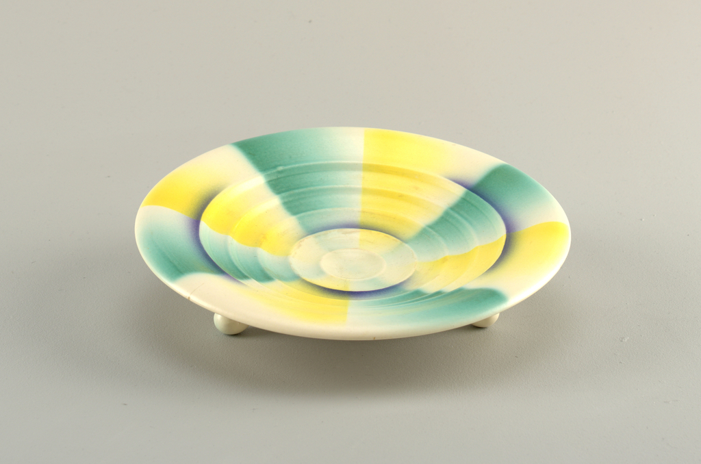 Circular dish with down curving edge resting on a base of three outturned ball feet.  Surface molded into concentric rings leading down to the center.  Overall pearlized surface.  White background with alternating areas of green and yellow radiating out from the center.  Four blue highlights evenly spaced over the surface.