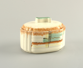 Oval shaped box with raised bottom rim.  Molded ends with vertical scalloped grooves and sides with horizontal scalloped bands.  Cream background with rust on the top edge, and an abstract design of lines and swatches of turquoise, yellow, rust, and dark brown on the two sides.  Oval cover with scalloped ends and protruding s-shaped finial.  Cream ground on cover with rust along the edge and green lining the top of the finial.