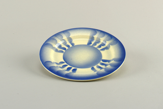 Circular dish with concave center with raised bottom rim.  Cream background with surface decoration in airbrushed blue.  Blue lines edge.  Centered circle connected to edge by four bands of three connected semicircles all facing clockwise.  Plates divided into quarters by these motifs.