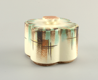 Quaterfoil-shaped box and lid.  Box has raised bottom rim.  Box is decorated from top edge with alternating airbrushed turquoise and brown stripes and then brown and yellow interlaced crosses and four stripes of airbrushed orange.  Lid has raised quatrefoil-shaped finial painted orange and is striped at edge with alternating airbrushed turquoise and brown.