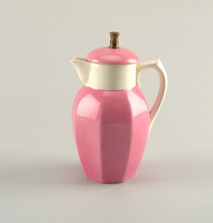 Cylindrical jug with pink body molded with angles.  Surmounted by a circular band of white with protruding spout sitting across from a curving white handle, connected to band and pink body.  Circular pink lid with tall metal finial on top and a metal strainer on the bottom to fit into the jug.