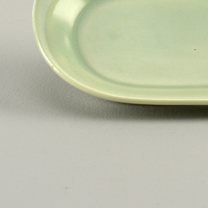 Tray that appears as if two half ovals were joined together about one half inch off-sides creating two curving tabs on either long side.  Entire surface covered with a speckled, light jade green ground.